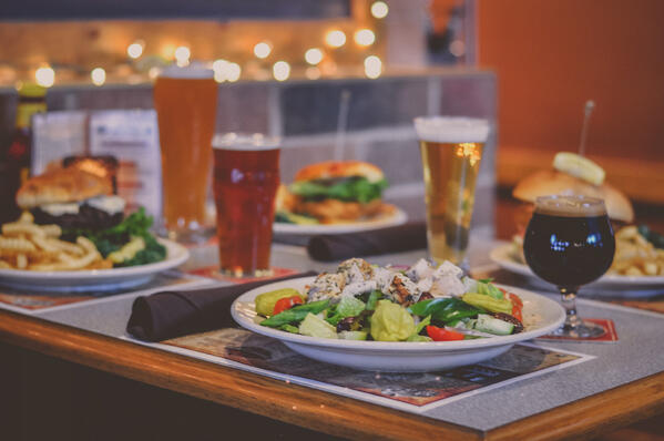 Beer and plates of food at restaurant table