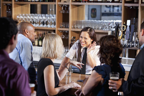 Smiling bartender serving crowd