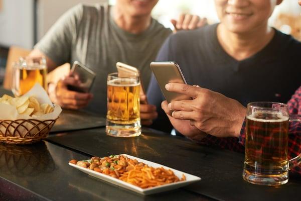 Men on phones at bar